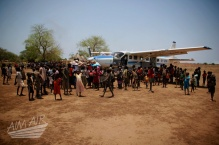 villagers gather to meet the AIM AIR plane